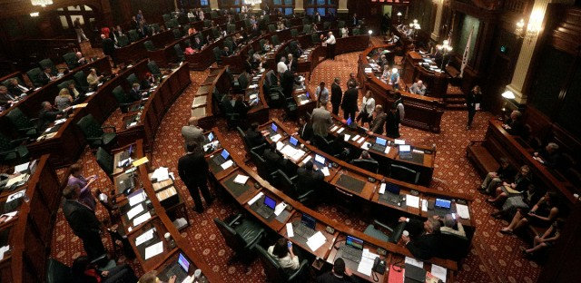 Illinois representatives gather on the House floor during session at the Illinois State Capitol Tuesday, May 31, 2016, in Springfield, Ill., as lawmakers press ahead on the last day of the spring legislative session. Illinois Gov. Bruce Rauner proposed a short-term budget fix on Tuesday in a last-ditch effort to give the state some temporary stability during a nearly yearlong spat between the Republican and Democratic lawmakers over a spending plan.