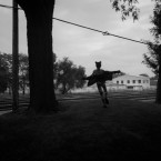A girl with arms outstretched runs through two trees as train tracks stretch out before her