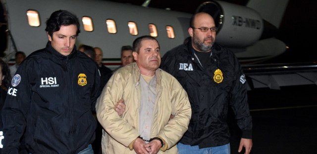 "Authorities escort Joaquin ""El Chapo"" Guzman to a waiting caravan of SUVs at Long Island MacArthur Airport on Thursday in Ronkonkoma, N.Y."