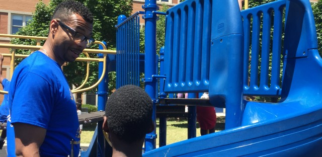 Principal Robert Croston speaks with a student on the playground of Jenner Academy of the Arts during an end-of-year celebration in June 2016.