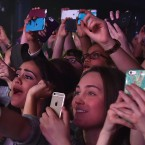 """Concertgoers use their cellphones during a Fifth Harmony concert March 23, 2015, in New York. The company Yondr created a locking pouch to hold phones during performances, creating a """"phone-free zone."""""""