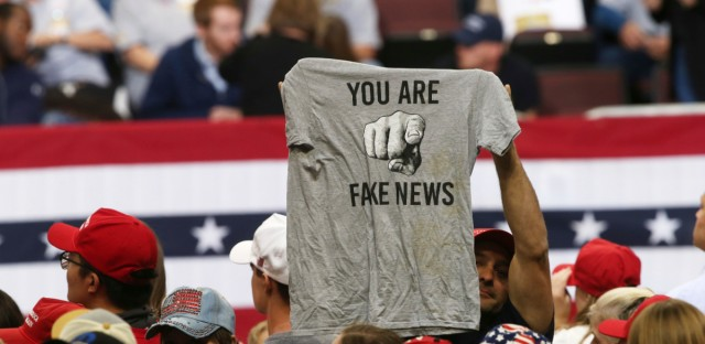 """In this Oct. 4 2018 file photo, a Trump supporter holds up a T-shirt reading """"You Are Fake News"""" before a rally by President Donald Trump in Rochester, Minn."""