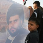 A young boy holds a poster of radical Shiite cleric Moqtada al-Sadr during a commemorative funeral march, Monday, Aug. 15, 2005, in Sadr City area of Baghdad, Iraq.