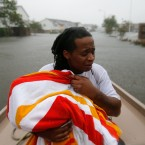 Demetres Fair holds a towel over his daughter Damouri Fair, 2, as they are rescued by boat by members of the Louisiana Department of Wildlife and Fisheries and the Houston Fire Department during flooding from Tropical Storm Harvey in Houston, Monday, Aug. 28, 2017.