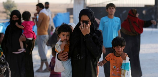A Syrian family who fled the battle between U.S.-backed Syrian Democratic Forces and the Islamic State militants from Raqqa city, arrive at a refugee camp, in Ain Issa town, northeast Syria on Monday, July 24, 2017.