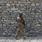 """FILE - In this April 17, 2017, file photo, a U.S. soldier patrols in Asad Khil village near the site of a U.S. bombing in the Achin district of Jalalabad, east of Kabul, Afghanistan. As the administration of President Donald Trump weighs sending more troops to Afghanistan, the 16-year war grinds on in bloody stalemate. Afghan soldiers are suffering what Pentagon auditors call """"shockingly high"""" battlefield casualties, and prospects are narrowing for a negotiated peace settlement with the Taliban."""