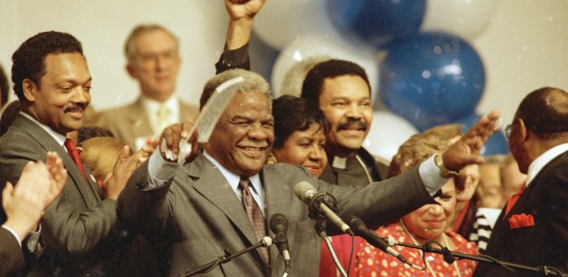 Harold Washington waves to cheering supporters on Tuesday night, April 7, 1987 as he announced victory in his bid for re-election as mayor of Chicago. At left is Rev. Jesse Jackson.