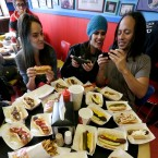 Carolyn Sweet, left, Stephanie Gannon, center, and Erik Luna, check cellular phone photographs of their food at Hot Doug's hotdog stand Wednesday, Oct. 1, 2014, in Chicago.