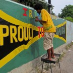 "A man paints a roadside wall mural saying ""Proud to be Jamaican"" in Kingston, Jamaica on Sunday, Aug. 5, 2012 during preparation for the island's 50th anniversary of independence from Britain."
