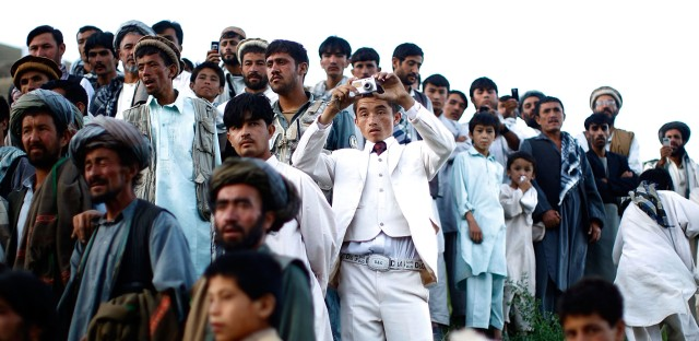 """Afghan president Hamid Karzai held a rally in a remote village, where he struck a deal with an influential religious leader. Thousands gathered for the campaign event. From the story """"Afghan President Karzai Rallies Support,"""" 2009."""