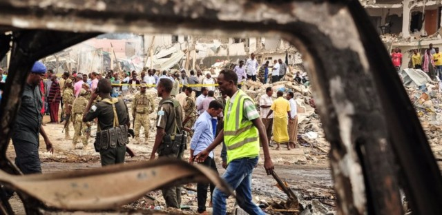Somali soldiers and rescue workers on Sunday inspect the scene of the truck bomb explosion in Mogadishu.
