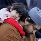 Three-year-old Alaa Sohim Chowdhury hugs her father Mohammed while he prays as worshippers gather during Eid al-Fitr morning services on Friday, Sept. 10, 2010, in Bridgeview, Ill. They were joined by Christian and Jewish religious leaders from around the Chicago area in a show of support for the Muslim community.