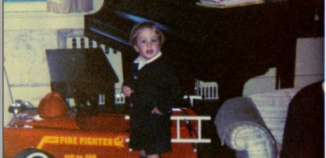 Welles Crowther as a young child, standing next to a toy fire truck. (Courtesy of The Crowther Family)