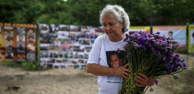 A woman who has a missing relative carries flowers at the site where almost 300 human remains were found in clandestine graves in Colinas de Santa Fe, Veracruz state, Mexico, Monday, Oct. 15, 2018. A Mass was held here Monday, one day before the Solecito Collective is to be honored by Notre Dame for its work locating the remains of missing people in Veracruz state. The Solecito Collective is made up people searching for their missing loved ones.