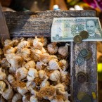 Cuban pesos sit on the edge of a bin filled with garlic bulbs at an outdoor food market in Havana, Cuba.