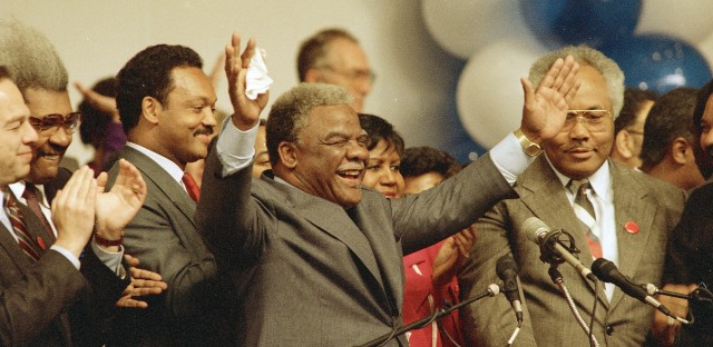 Harold Washington waves to cheering supporters on Tuesday night, April 7, 1987 as he announced victory in his bid for re-election as mayor of Chicago. At left is Rev, Jesse Jackson.