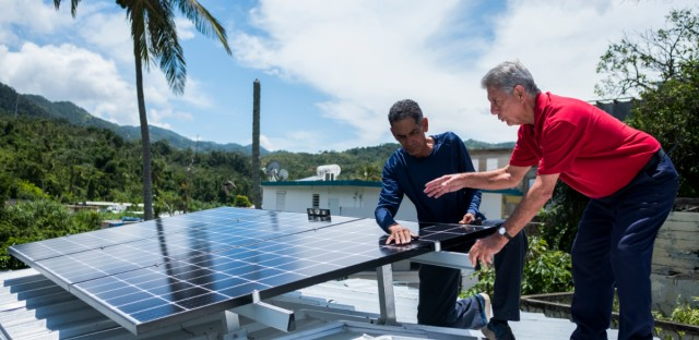 In this July 24, 2018 photo, Julio Rosario, left, instals a solar energy system with the founder of the nonprofit environmental group Casa Pueblo Alexis Masol, in Adjuntas, Puerto Rico. The nonprofit environmental group Casa Pueblo has installed solar systems at two hardware stores, one barber shop and several corner stores that activists hope will serve as a power oasis where people can charge their phones and store medications during a storm if needed.