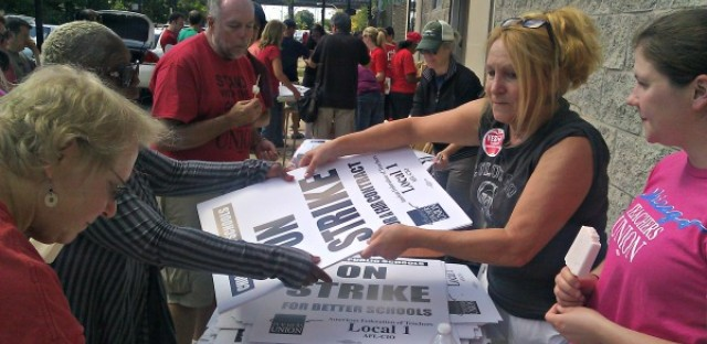 Teachers pick up 'on strike' signs Saturday at a 'strike headquarters' the Chicago Teachers Union has set up.