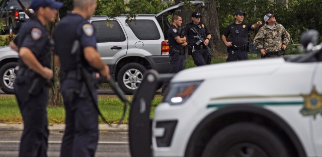 Law enforcement officers man a road block in Baton Rouge after Multiple law enforcement officers were killed and wounded Sunday morning.