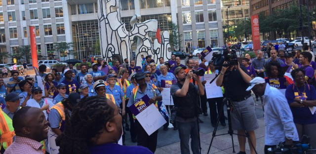 More than a hundred workers and supporters rally at the Thompson Center before a march around city hall in Chicago.