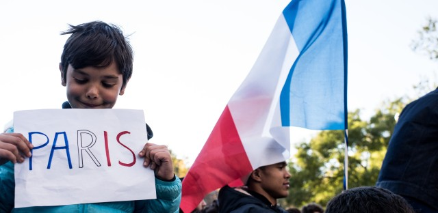 People hold signs and flags while attending a vigil held for the victims of the Paris terror attacks in Washington Square Park on November 14, 2015, in New York City. Searches related to the deadly attacks in Paris were among the most popular Google queries of the year.
