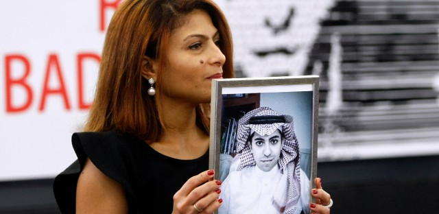 FILE - In this Dec, 16, 2015 file photo, Ensaf Haidar, wife of the jailed Saudi Arabian blogger Raif Badawi, shows a portrait of her husband as he is awarded the Sakharov Prize, in Strasbourg, France. Saudi Arabia has given Canada's ambassador 24 hours to leave the kingdom after Canada criticized the recent arrest of women's rights activists. Among the arrested activists is Samar Badawi, whose writer brother Raif Badawi was arrested in Saudi Arabia in 2012 and later sentenced to 1,000 lashes and 10 years in prison for insulting Islam while blogging.
