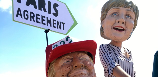 Oxfam activists wearing masks of US President Donald Trump, left, and German Chancellor Angela Merkel stage a demonstration in Giardini Naxos, near the venue of the G7 summit in the Sicilian town of Taormina, southern Italy, Friday, May 26, 2017. Climate change promises to be the most problematic issue for this summit after Trump's decision to review U.S. policies related to the Paris Agreement on fighting global warming.