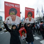 "Protesters with pictures of South Korean President Park Geun-hye march toward the presidential house during a rally calling for Park to step down in Seoul, South Korea, Wednesday, Nov. 30, 2016. South Korea's three main opposition parties agreed Wednesday to stick to their plans to impeach Park, dismissing as a stalling tactic offered by her to resign if parliament arranges a safe transfer of power. The letters read ""Park Geun-hye to step down""."