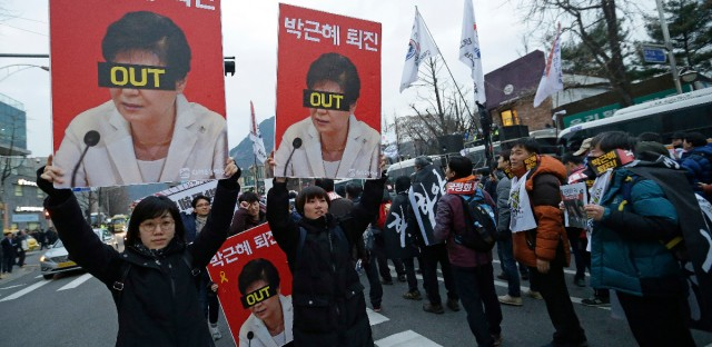 "Protesters with pictures of South Korean President Park Geun-hye march toward the presidential house during a rally calling for Park to step down in Seoul, South Korea. South Korea's three main opposition parties agreed Wednesday to stick to their plans to impeach Park, dismissing as a stalling tactic offered by her to resign if parliament arranges a safe transfer of power. The letters read ""Park Geun-hye to step down""."