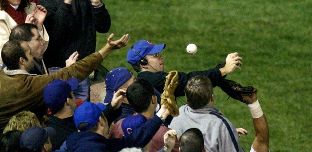 In this Oct 14, 2003, file photo, Steve Bartman catches a ball as Chicago Cubs left fielder Moises Alou's arm is seen reaching into the stands, at right, against the Florida Marlins in the eighth inning during Game 6 of the National League championship series Tuesday, Oct. 14, 2003, at Wrigley Field in Chicago. Bartman's spokesman, Frank Murtha, tells USA Today that Bartman is overjoyed by the Cubs first World Series title since 1908, but won't attend the victory parade in Chicago on Nov. 4, 2016.