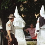 A Forsyth County, Ga., sheriff deputy watches two robed members of the Rebel Knights of the Ku Klux Klan walk past during a demonstration at the county courthouse in Cumming, Georgia Saturday, July 15, 1995. About 30 Klansmen and women rallied against illegal aliens while double that number tourned out to oppose them.