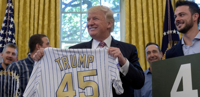 President Donald Trump holds up a Chicago Cubs jersey as he meets with members of the 2016 World Series Champions Chicago Cubs, Wednesday, June 28, 2017, in the Oval Office of the White House in Washington. Cubs third baseman Kris Bryant is at right.