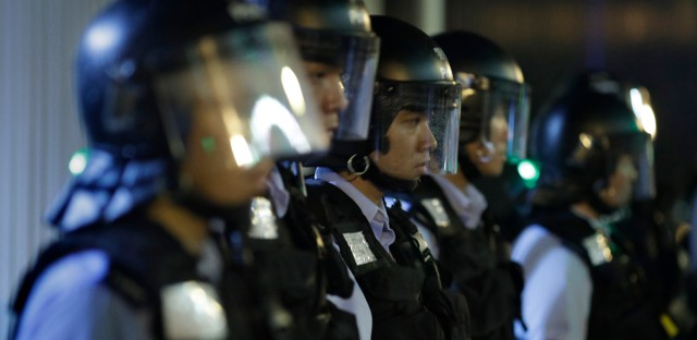 Policemen in anti-riot gear stand guard outside the Legislative Council in Hong Kong, Tuesday, June 11, 2019. Opponents of legislation in Hong Kong that would allow criminal suspects to be extradited to mainland China gathered outside the Legislative Council on Tuesday night ahead of a day of expected demonstrations and labor strikes.