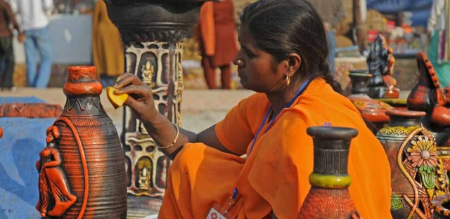An artist giving finishing touches to her clay pottery work at the annual Surajkund Crafts Mela near Delhi.