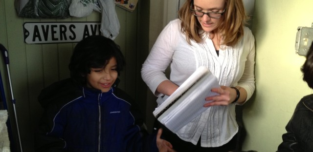 Joaquin Camacho talks with Rachel Perveiler as she checks in books. Perveiler uses a spiral notebook to keep track of what books are currently checked out.