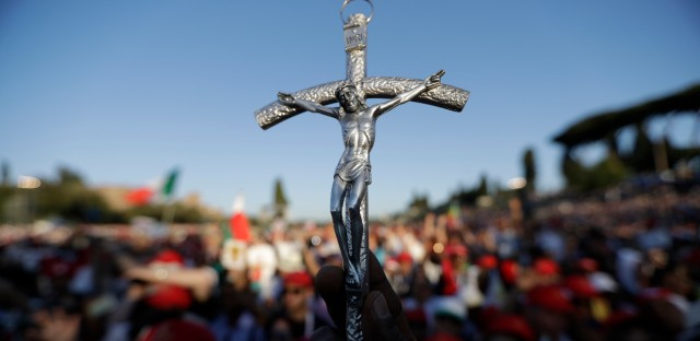 A man holds a crucifix during a Pentecost vigil prayer lead by Pope Francis at Rome's Circus Maximus.