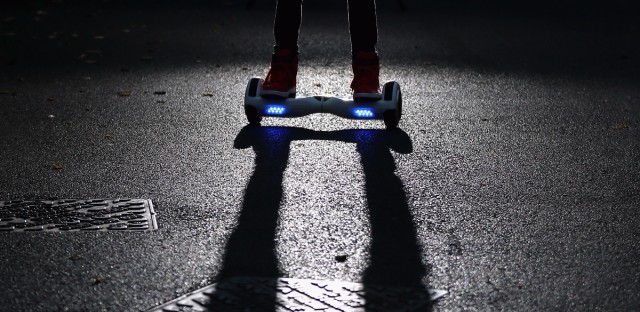 A youth poses as he rides a hoverboard, which is also known as a self-balancing scooter and balance board, last October in Knutsford, England. More than half a million of the devices have been recalled in the United States, after nearly 100 instances of the boards catching fire.