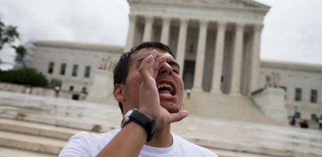 Gerson Quinteron of Washington yells during a demonstration on immigration, Thursday, June 23, 2016, outside the Supreme Court in Washington.