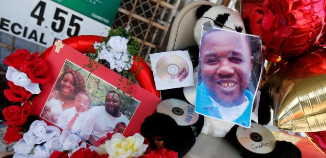 Photos of Alton Sterling are interspersed with flowers and mementos at a makeshift memorial in front of the Triple S Food Mart in Baton Rouge, La. Sterling, 37, was shot and killed outside the convenience store by Baton Rouge police, where he was selling CDs.