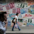People walk past a money exchange shop decorated with different currencies in Hong Kong, Monday, June 27, 2016. Japanese and Chinese stocks rose Monday but other Asian markets declined, crude prices fell further and U.S. shares appeared headed for a lower opening as jittery traders watched for more fallout from Britain's vote to exit the European Union.