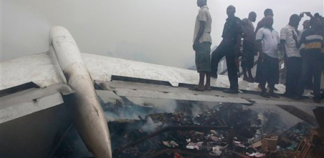 People stand on a wing of a wrecked passenger plane in Lagos, Nigeria on June 3, 2012. The plane crashed in a densely populated neighborhood near the airport.
