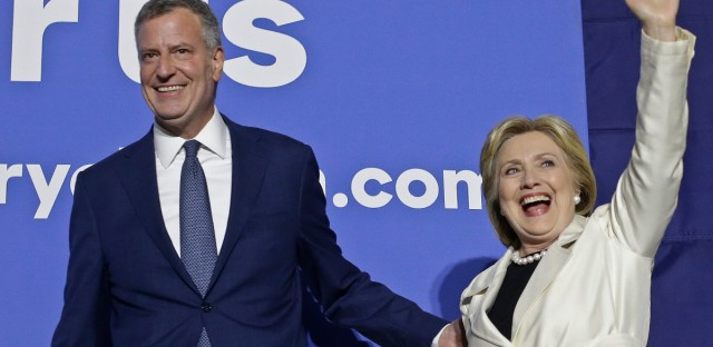 New York City Mayor Bill de Blasio, left, leads Democratic presidential candidate Hillary Clinton on stage as she waves to supporters after the CNN Democratic Presidential Primary Debate Thursday, April 14, 2016, in New York.