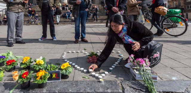 A woman places candles in the shape of a heart outside the stock exchange in Brussels. Explosions, at least one likely caused by a suicide bomber, rocked the Brussels airport and subway system Tuesday.