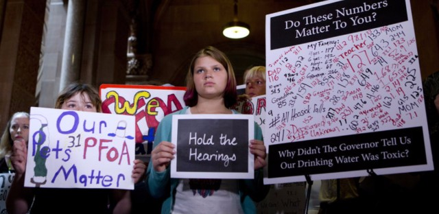 Protesters in Hoosick Falls, N.Y., in June hold signs calling for hearings on contamination in their town's drinking water by a chemical related to firefighting foam.