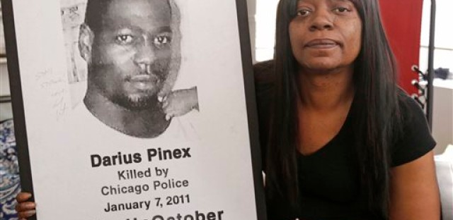 Gloria Pinex holds a photo of her son Darius Pinex, Thursday, Dec. 17, 2015 at her home in Chicago. Darius was killed by Chicago police in 2011. A top city lawyer stepped down after a federal judge accused him of hiding evidence in the case.