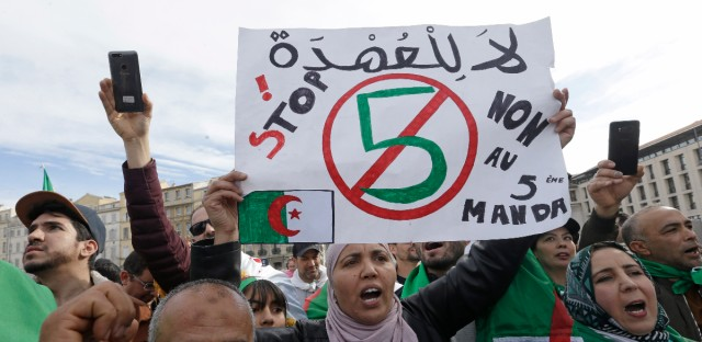 """A demonstrator holds up a sign that reads, """"no to a 5th term"""" during a protest to denounce President Abdelaziz Bouteflika's bid for a fifth term, in Marseille, southern France, Sunday, March 3, 2019. Algeria's Constitutional Council has been placed under high security as President Abdelaziz Bouteflika's bid for a fifth term is due to be formally submitted."""