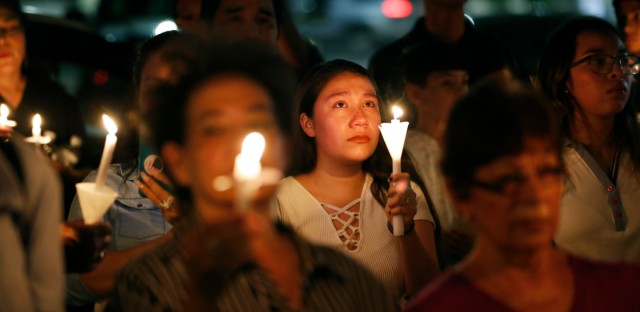 People attend a candlelight vigil for victims of a mass shooting at a shopping complex over the weekend, Monday, Aug. 5, 2019, in El Paso, Texas.