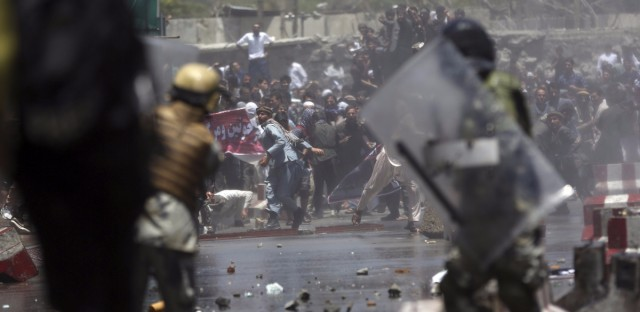 Protesters throw stones at security forces during a demonstration in Kabul on Friday. Several demonstrators were killed during clashes with Afghan law enforcement after gathering to protest the security situation in the capital after Wednesday's deadly bombing.