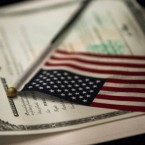 An American flag rests on a Certificate of Citizenship during a naturalization ceremony at the Lower East Side Tenement Museum, Tuesday, Nov. 15, 2016, in New York. (AP Photo/Mary Altaffer)