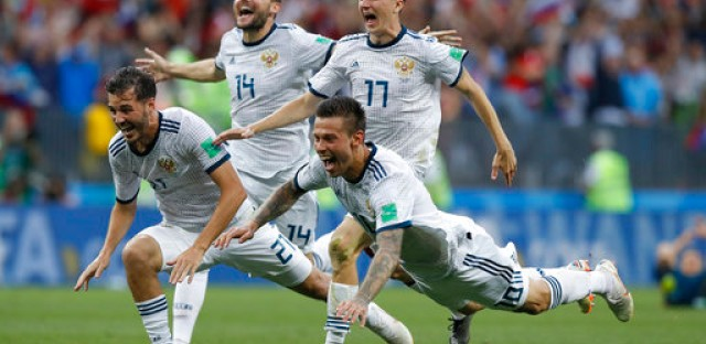 In this Sunday, July 1, 2018 file photo Russia's Fyodor Smolov, right, dives as he celebrates with teammates after Russia defeated Spain in a penalty shoot out during the round of 16 match between Spain and Russia at the 2018 soccer World Cup at the Luzhniki Stadium in Moscow, Russia.